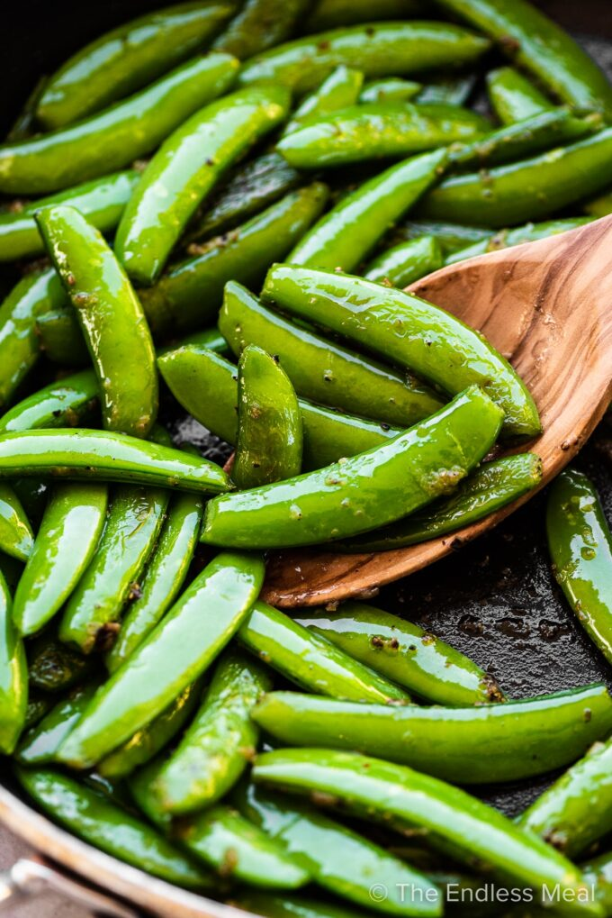 Sugar snap peas getting cooked in a pan with garlic butter.
