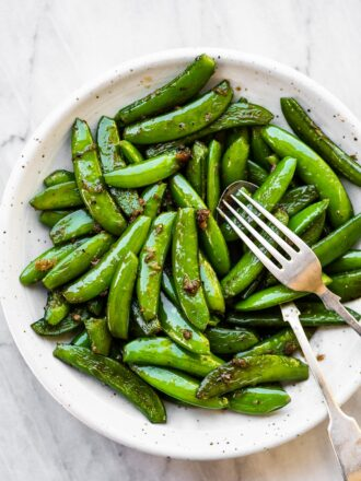 Garlic butter sugar snap peas in a white serving bowl.