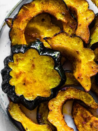 Roasted acorn squash on a serving plate.