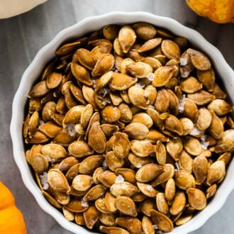 A white bowl of roasted pumpkin seeds surrounded by pumpkins.