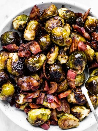 A serving bowl filled with roasted brussels sprouts with bacon.