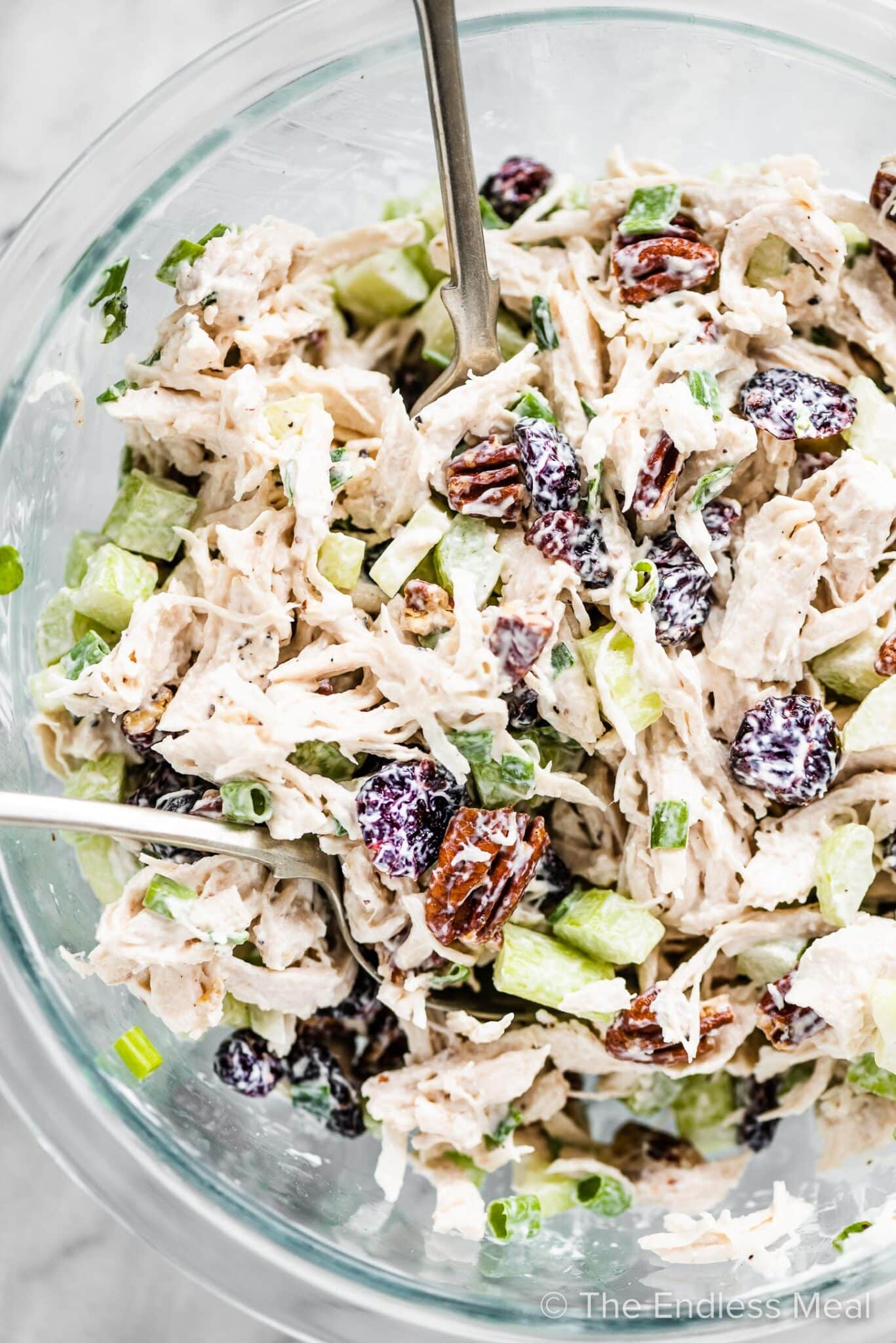 Cranberry chicken salad in a glass mixing bowl with serving spoons.