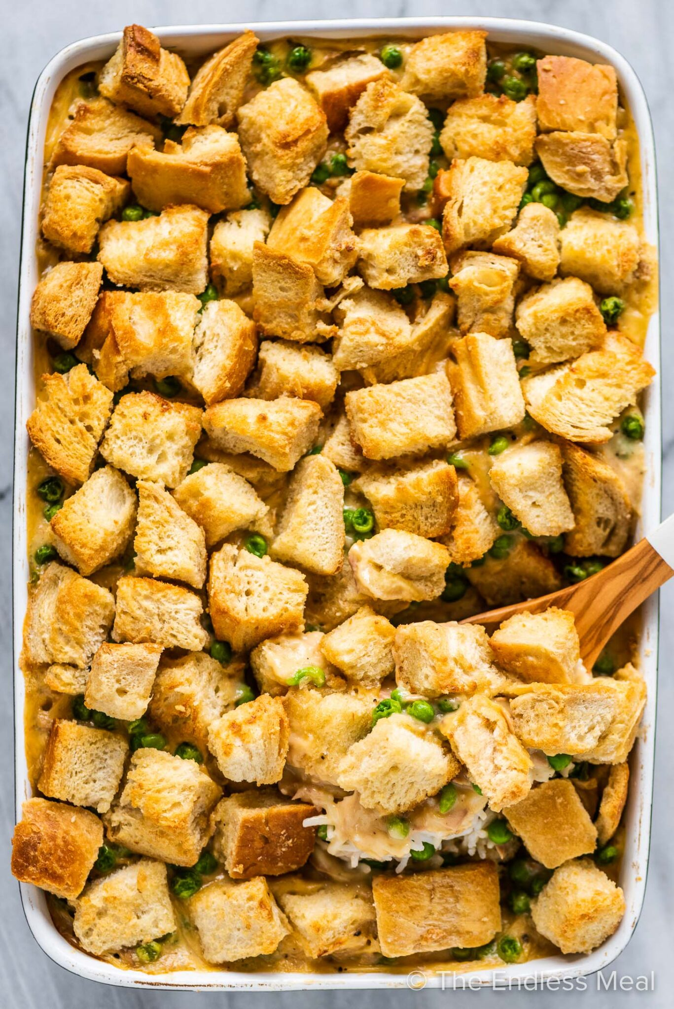 A casserole dish with tuna rice casserole and lots of croutons on top.