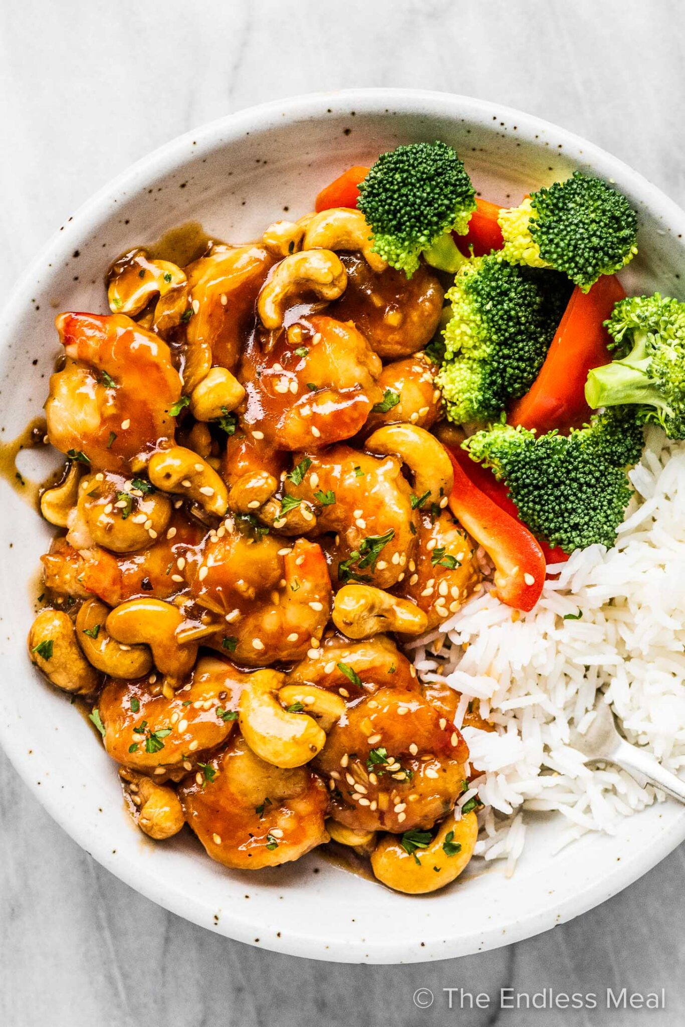 Cashew shrimp in a white bowl with broccoli and rice.