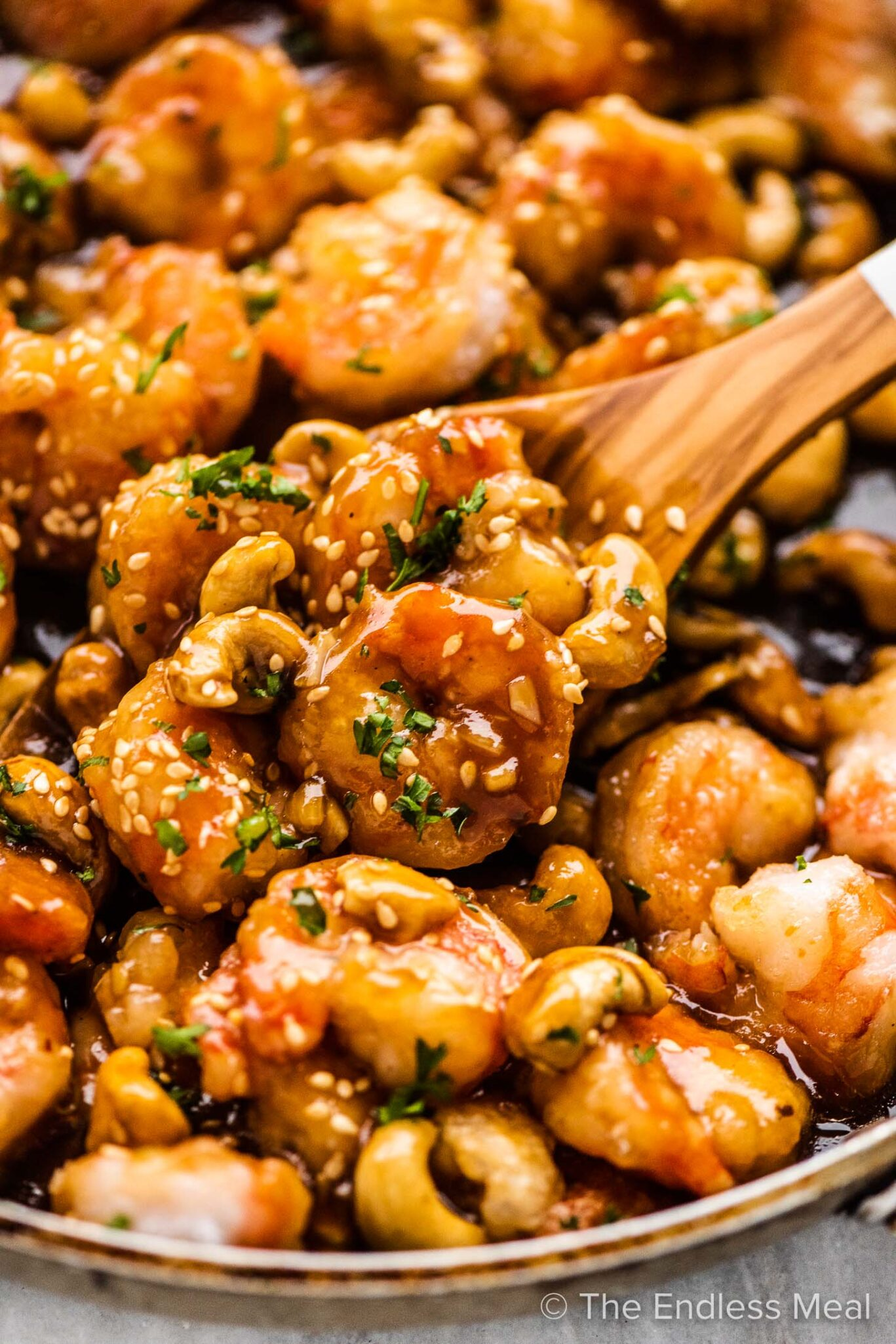 A closeup of shrimp with cashew nuts in a frying pan.