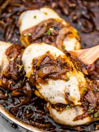 A spoon scooping French onion chicken out of a pan.