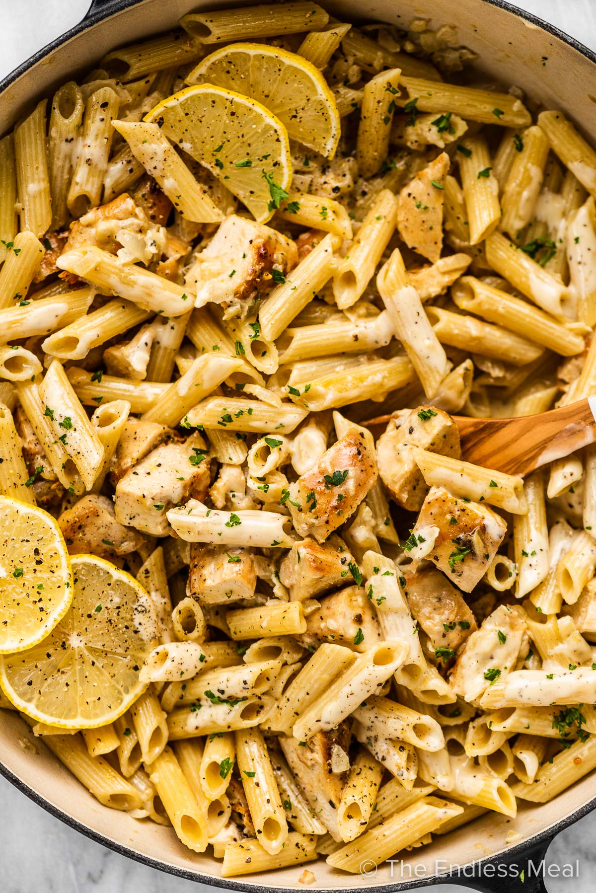 A close up of lemon chicken pasta in a pan with a wooden spoon.