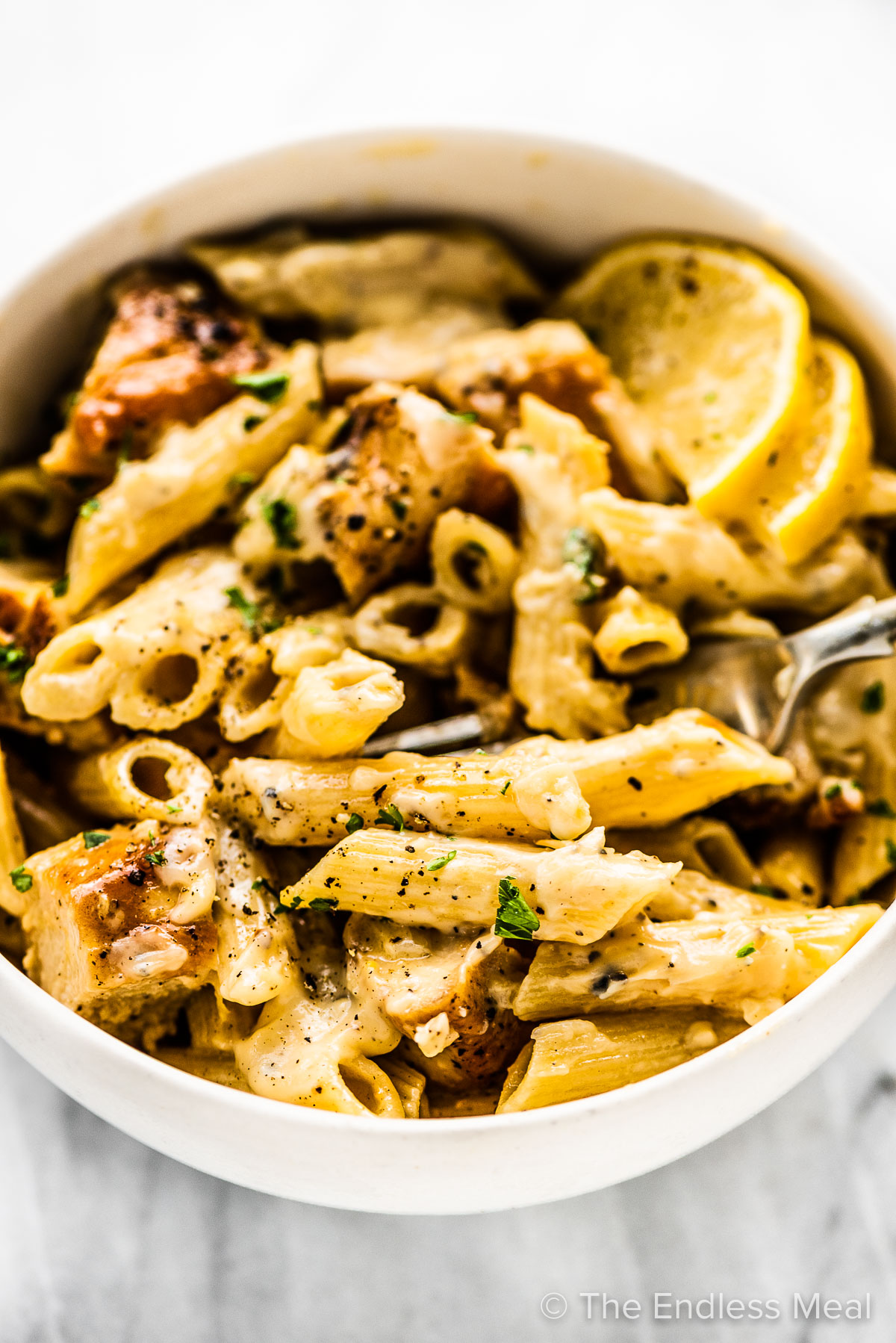 Lemon chicken pasta in a bowl with a fork and lemon slices.