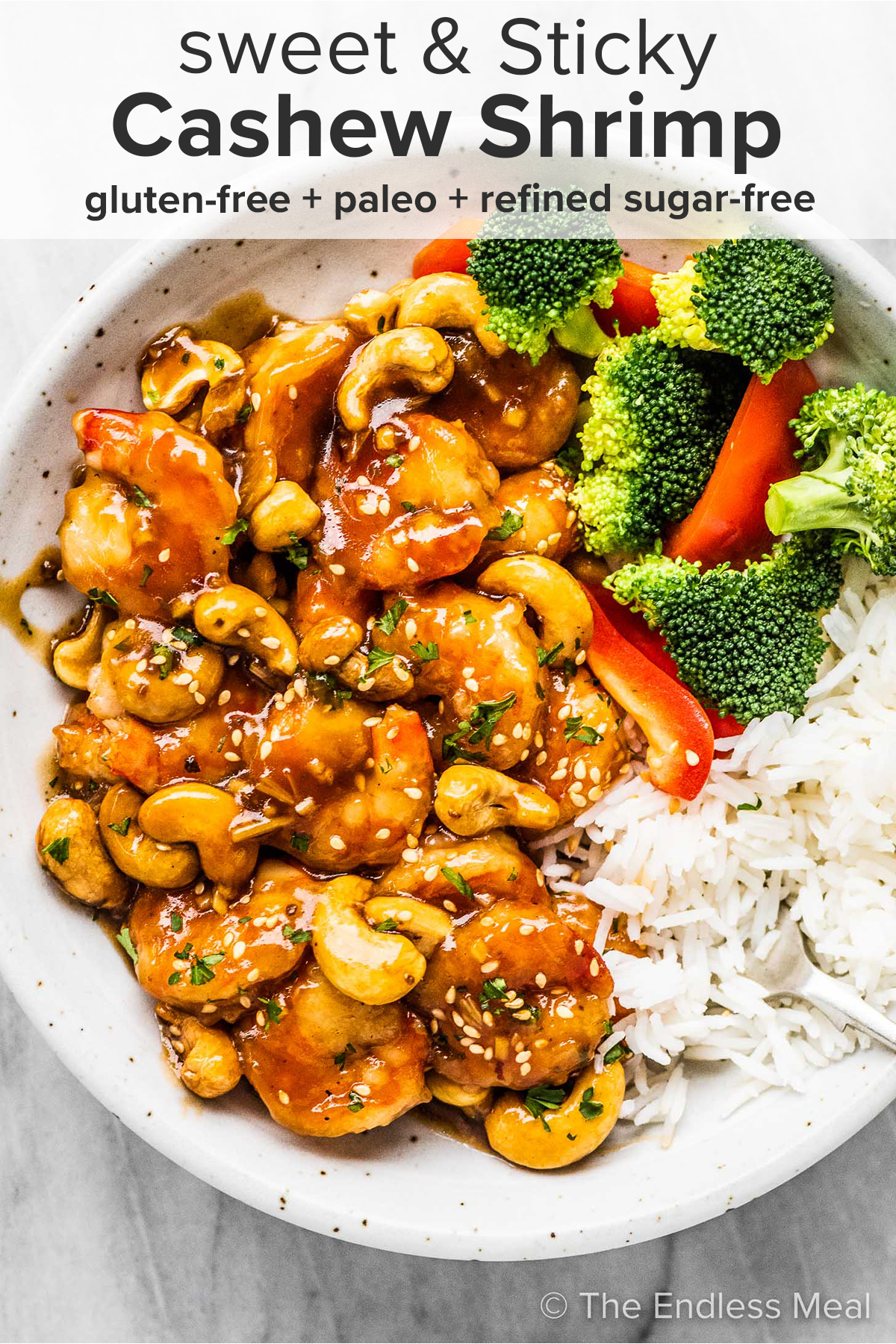 Cashew shrimp in a white bowl with broccoli and rice with the recipe title on top of the picture.