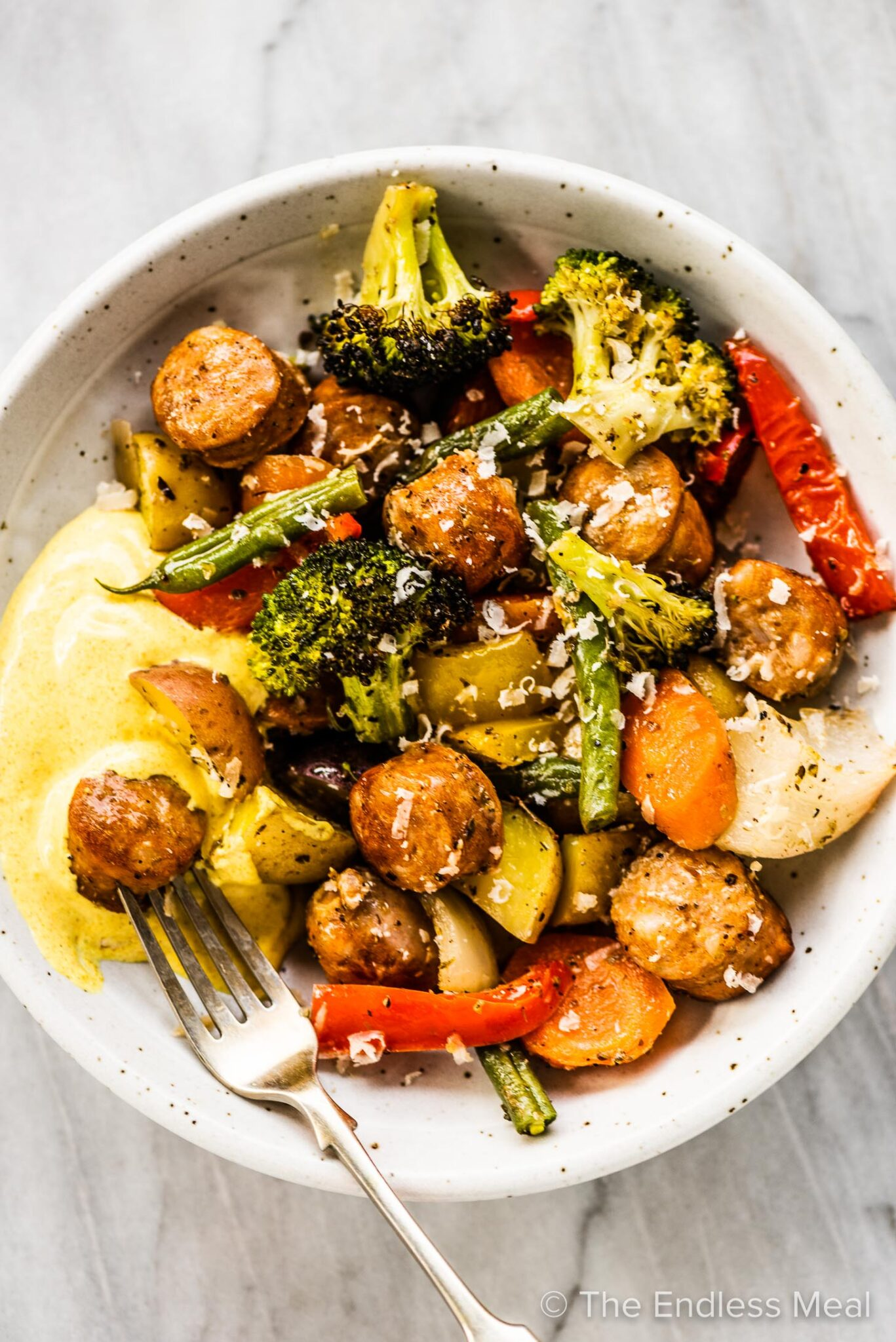 A dinner bowl with sheet pan sausages and veggies and a dipping sauce.