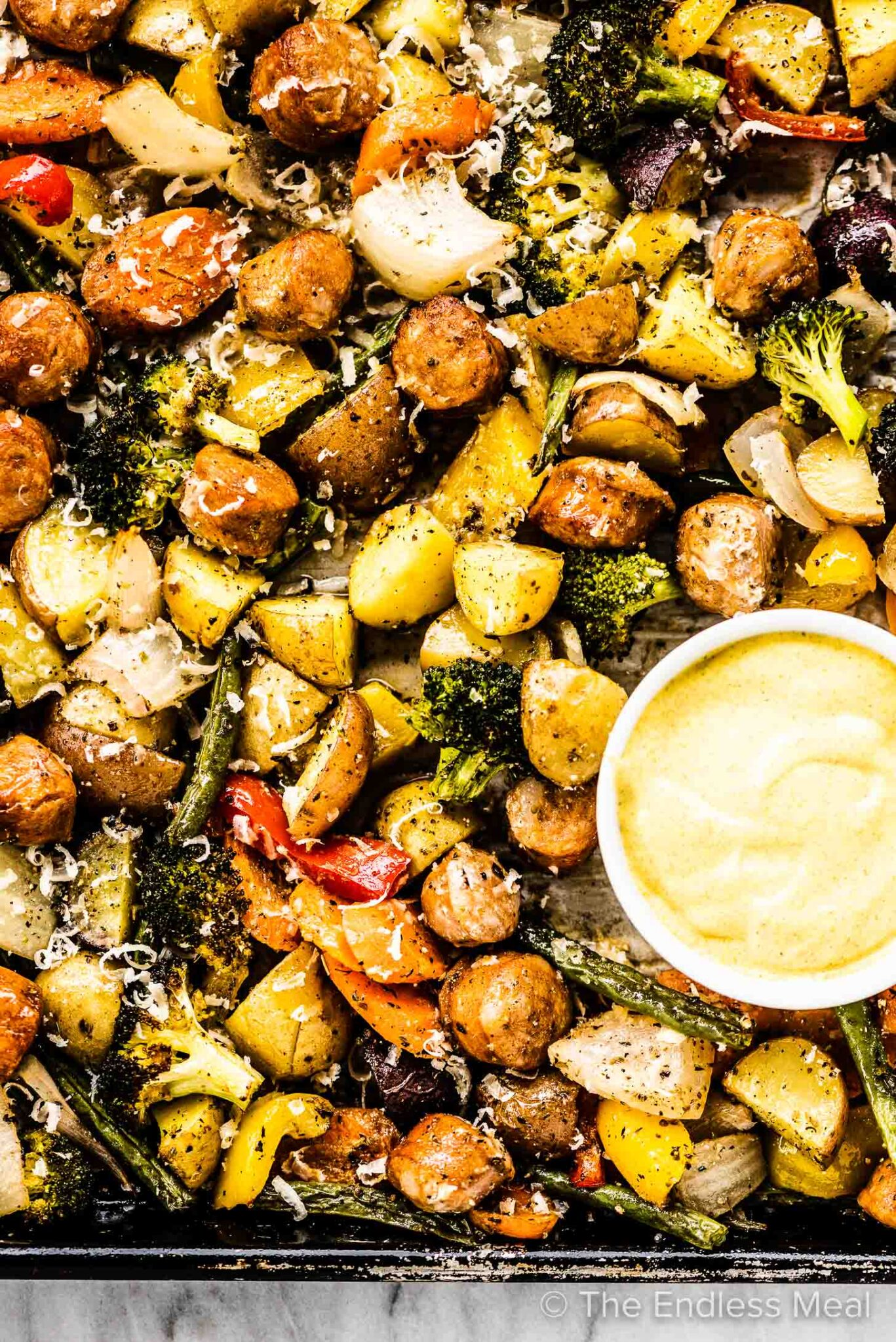 Sheet pan sausages and veggies on a baking sheet with a bowl of dipping sauce.