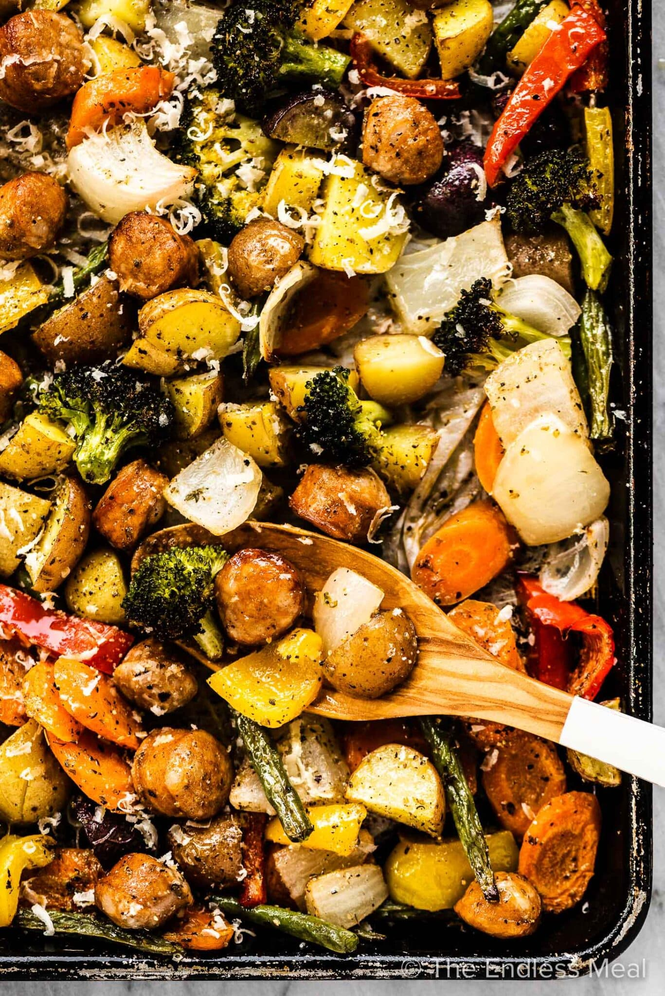 A sheet pan filled with roasted sausages and veggies.