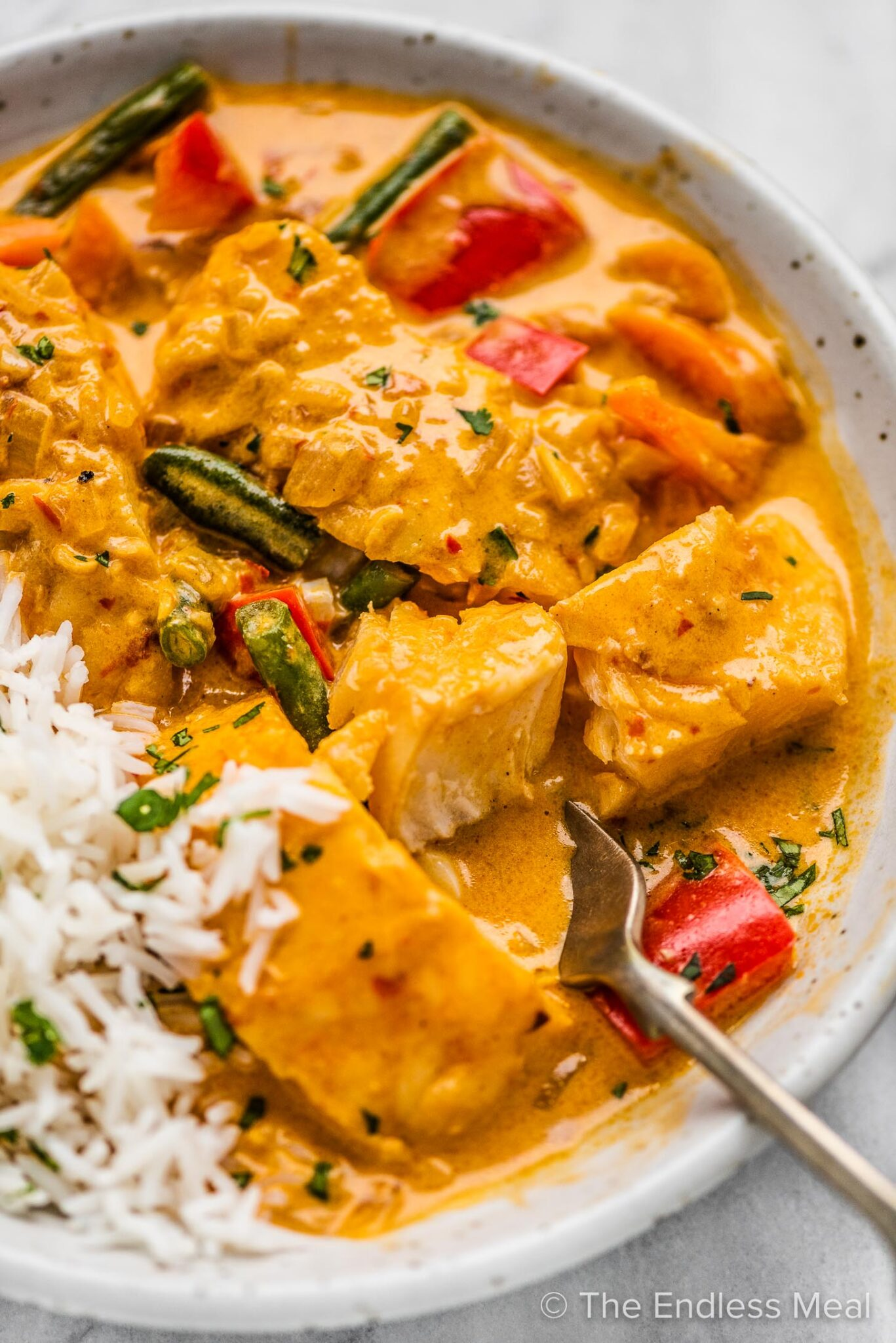 A closeup of a fork taking a piece of Thai fish curry out of a bowl.