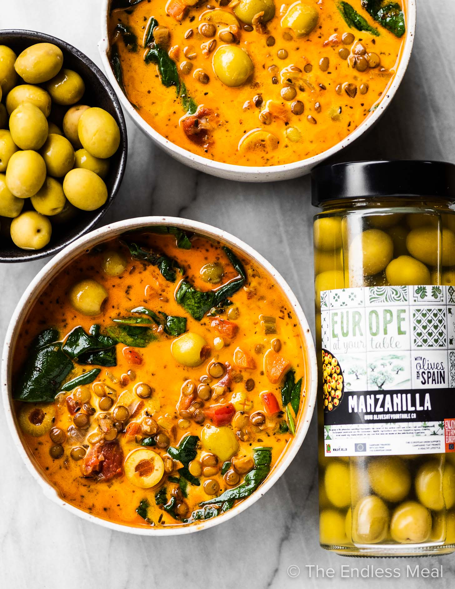 A jar of European olives next to bowls of soup.
