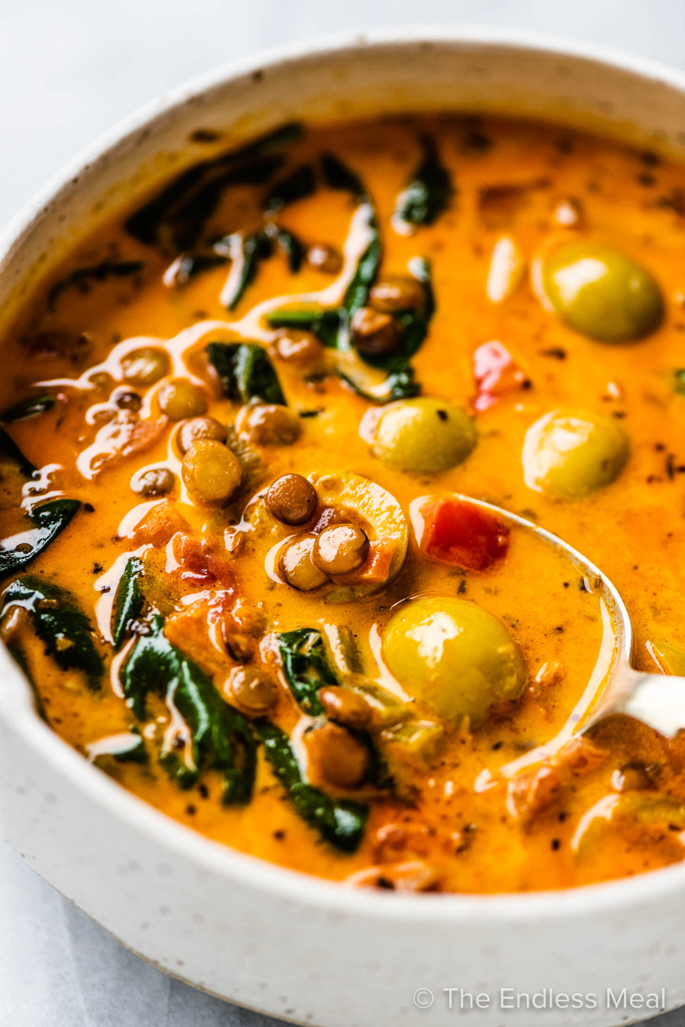 A spoon in a bowl of tomato lentil soup with olives.