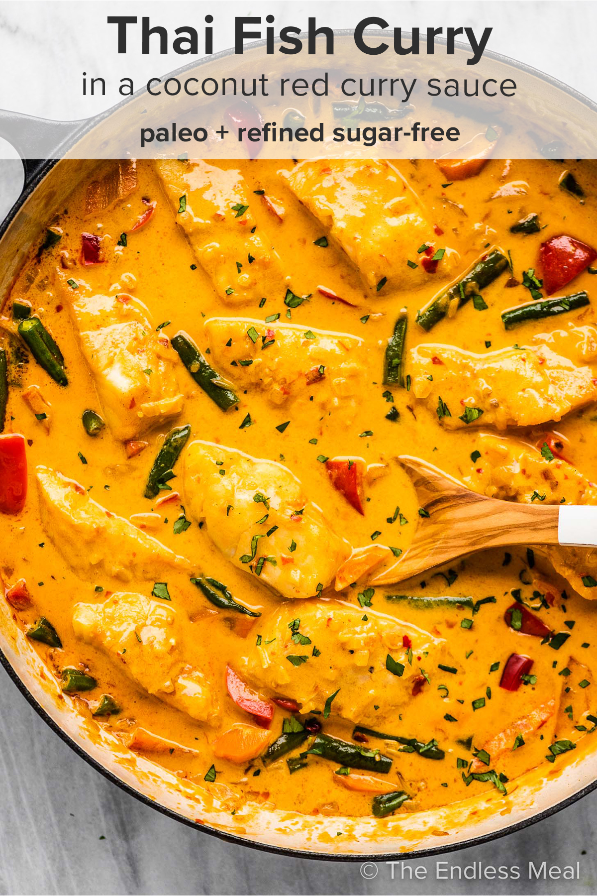 A pan of Thai fish curry with a wooden spoon inside and the recipe title on top of the picture.