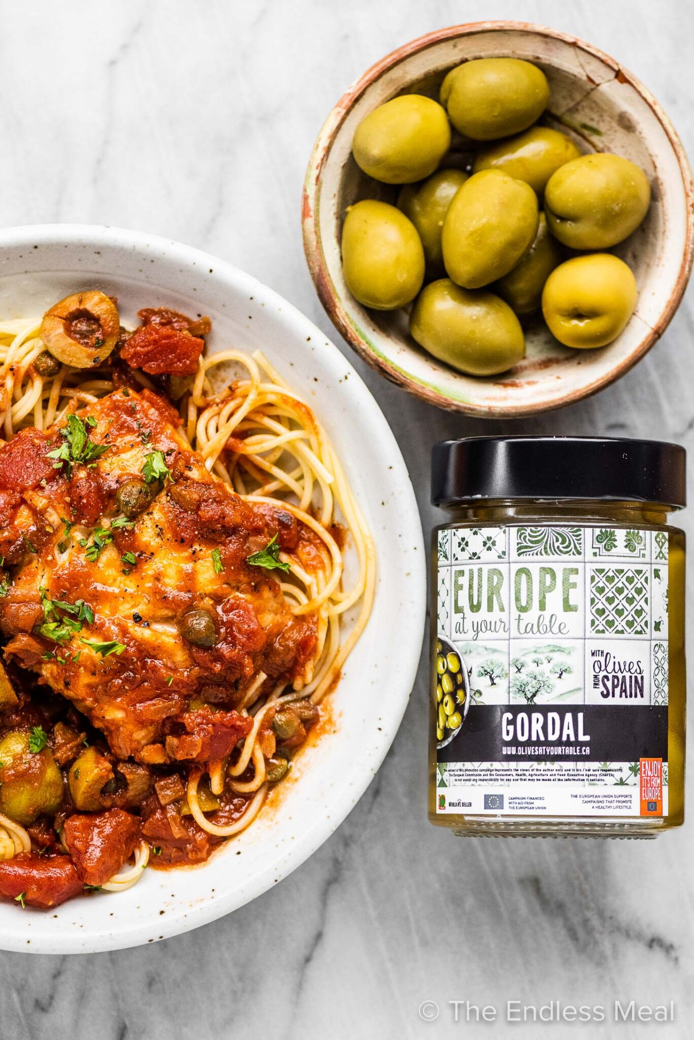 A jar of Gordal olives beside a plate of pasta with cod.