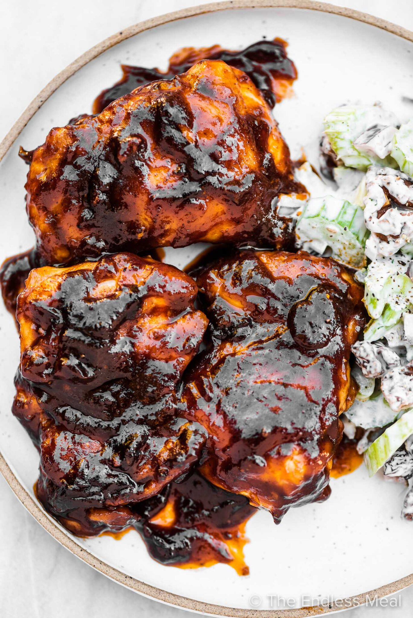 Stovetop BBQ chicken on a plate with celery salad.