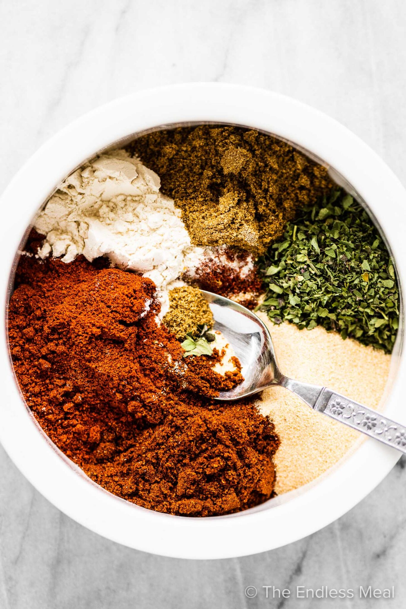 The spices in taco seasoning in a white bowl.