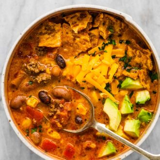 A bowl of taco soup with cheddar cheese and avocado on top.