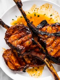 Oven grilled tomahawk pork chops piled on a white plate.