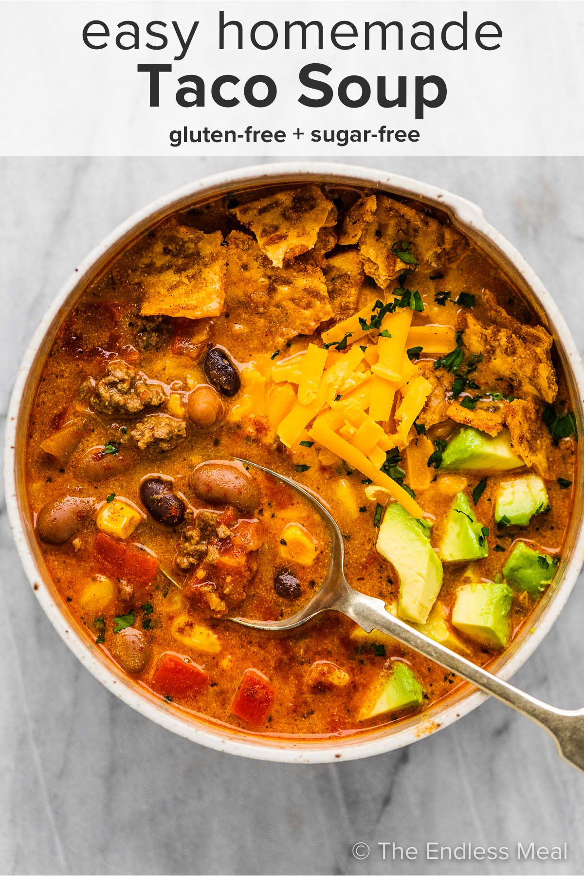 Taco soup in a bowl with a spoon and the recipe title on top of the picture.