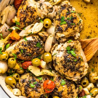 Chicken provencal in a braising pan with a wooden spoon.