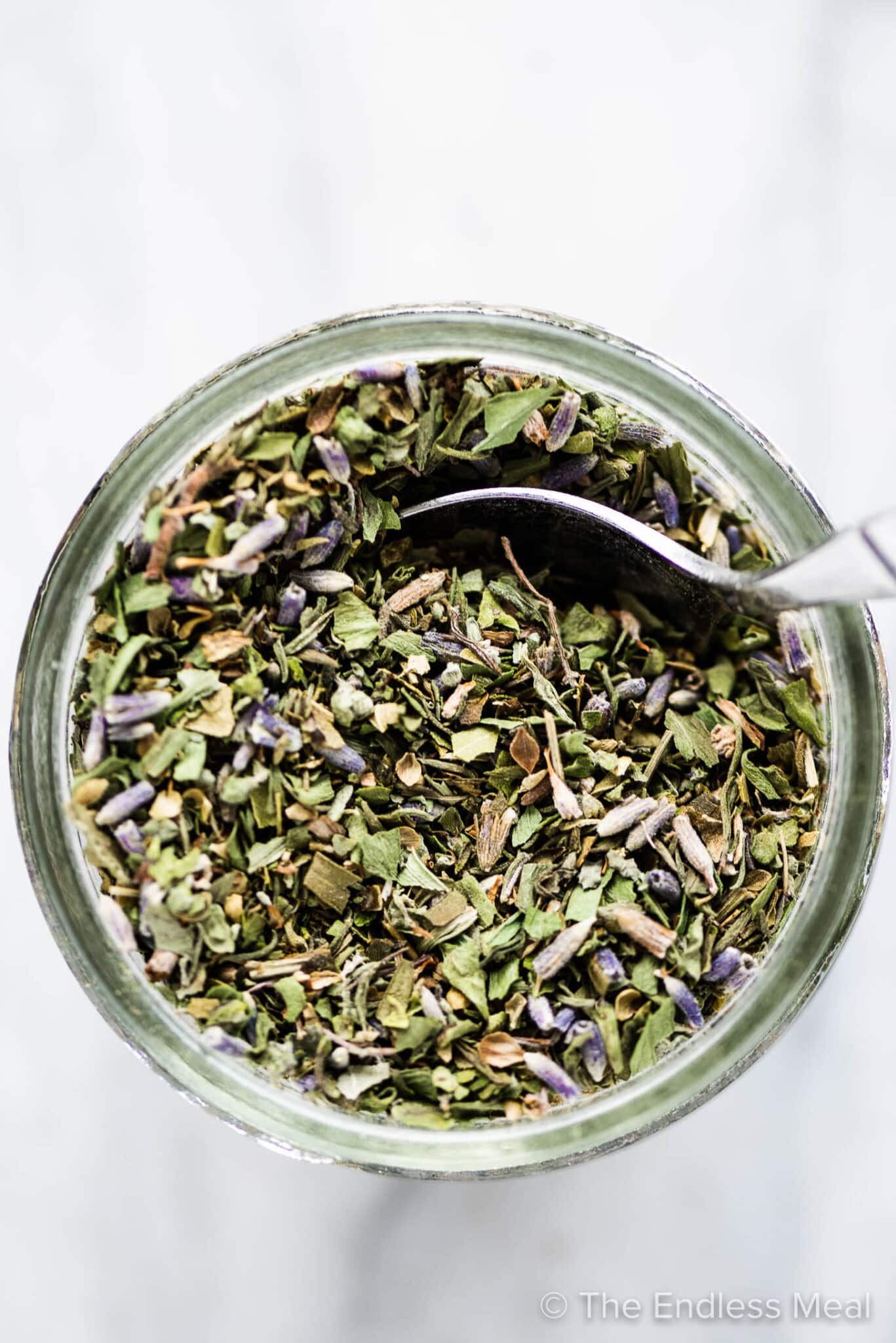 A jar of herbs de provence with a spoon inside.