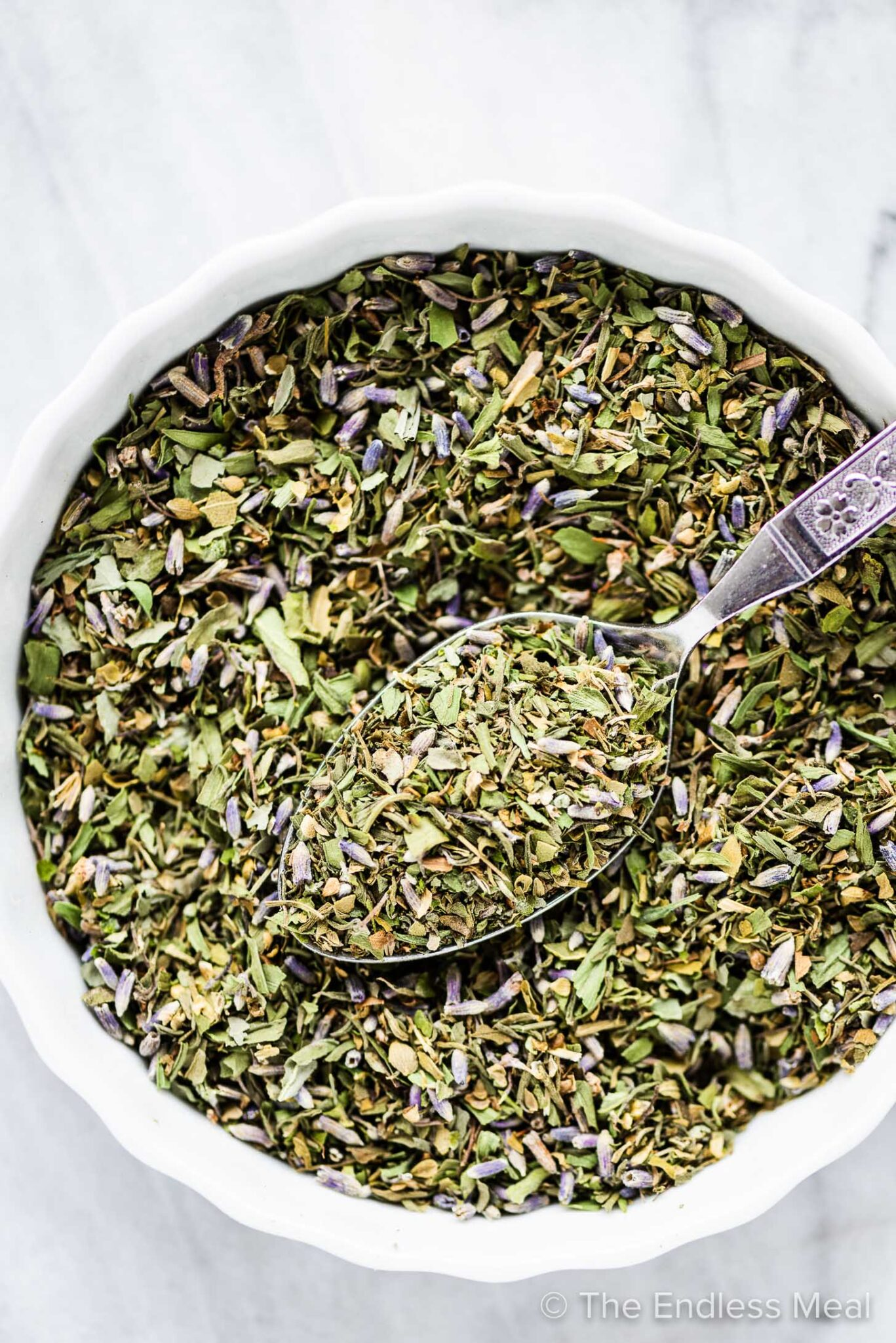 A bowl with herbs de provence and a spoon mixing it.