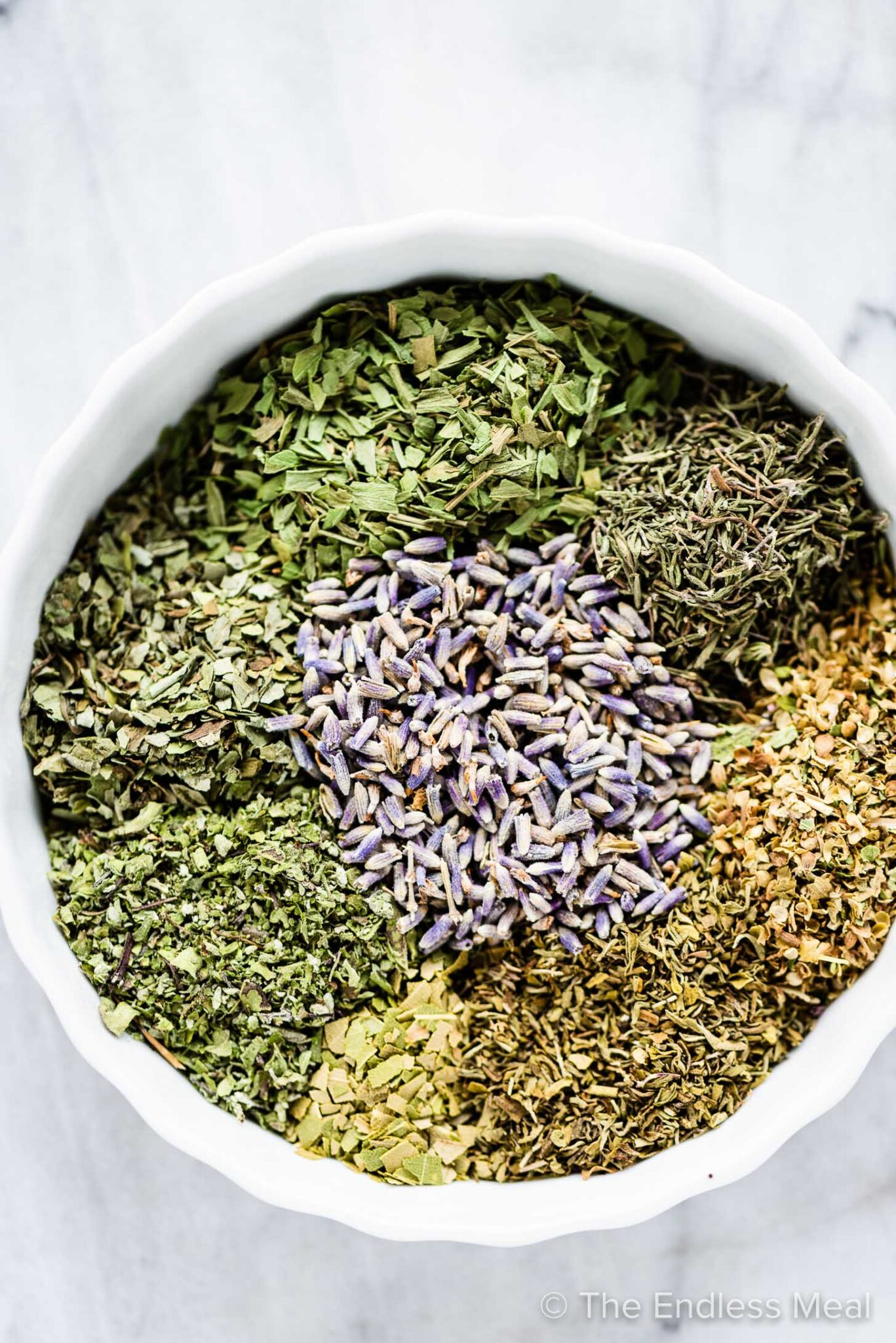 The spices for herbs de provence placed in a shallow white bowl.