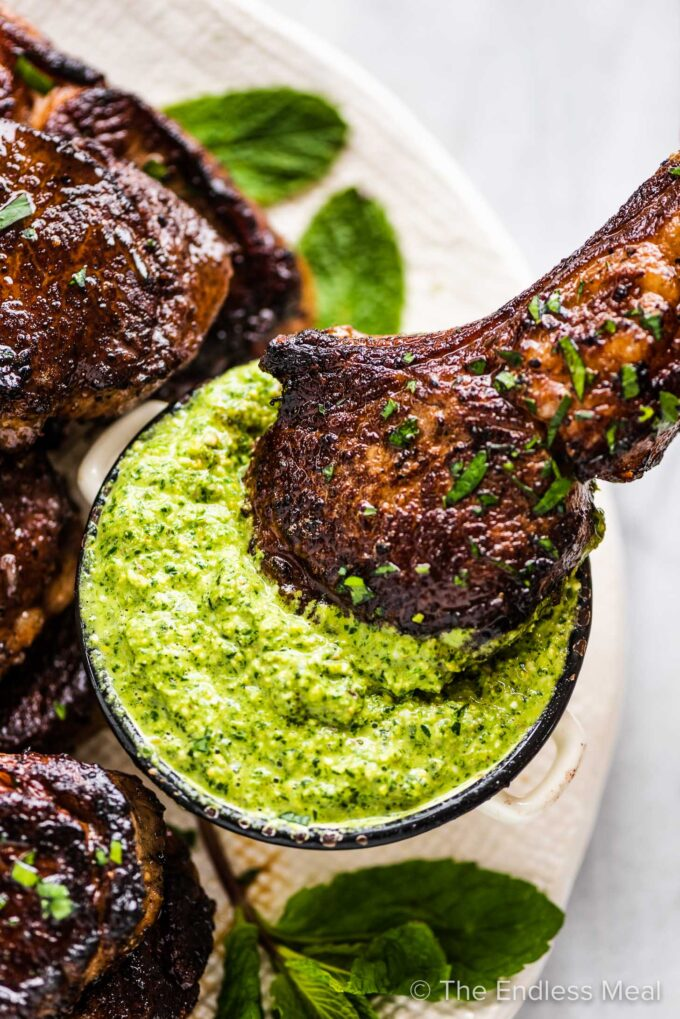 A lamb lollipop being dipped into mint pesto.