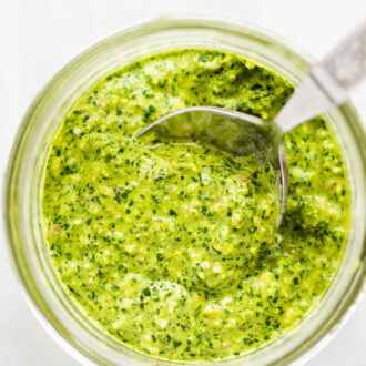 Mint pesto in a glass jar with a spoon.