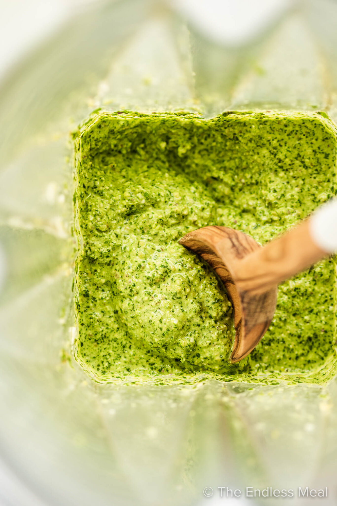 Mint pesto in a blender with a wooden spoon.