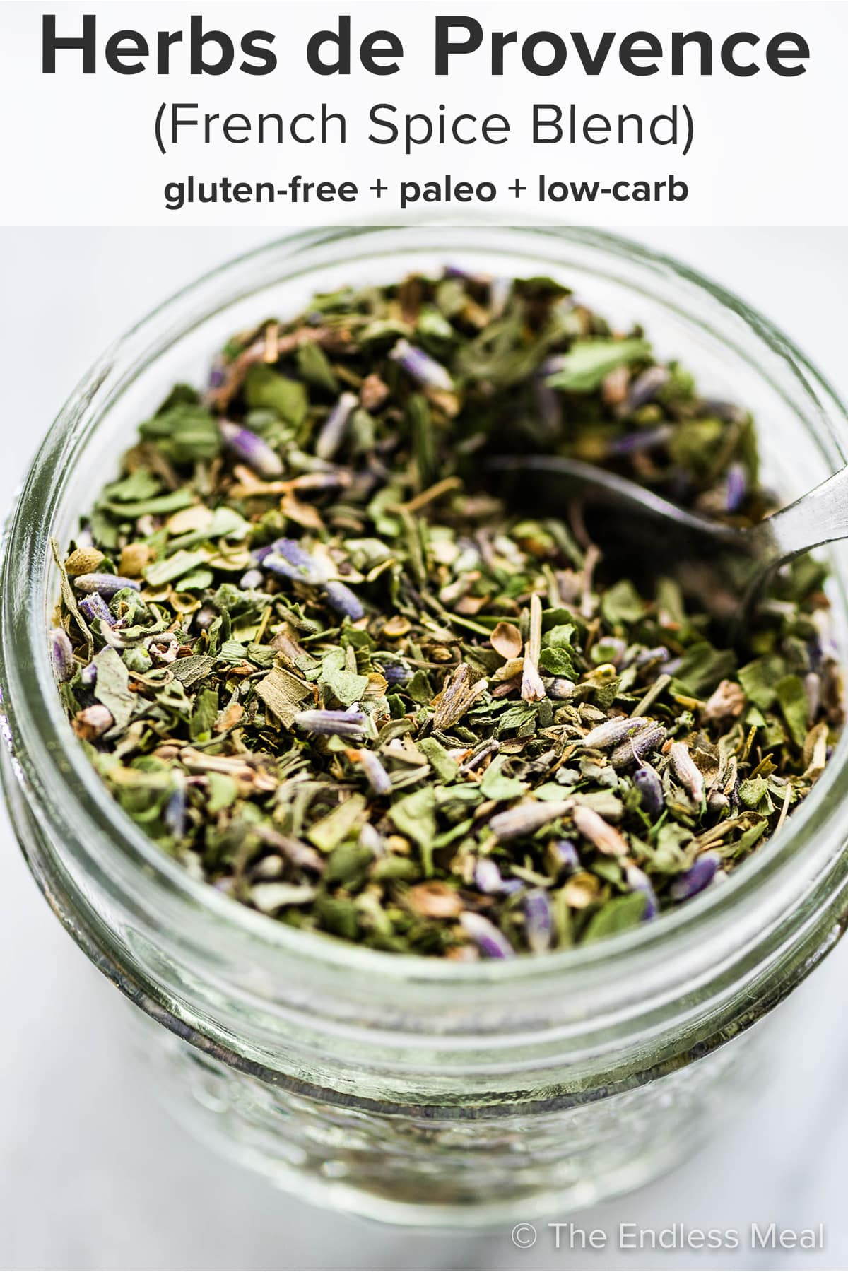 A jar of herbs de provence with a spoon inside and the recipe title on top of the picture.