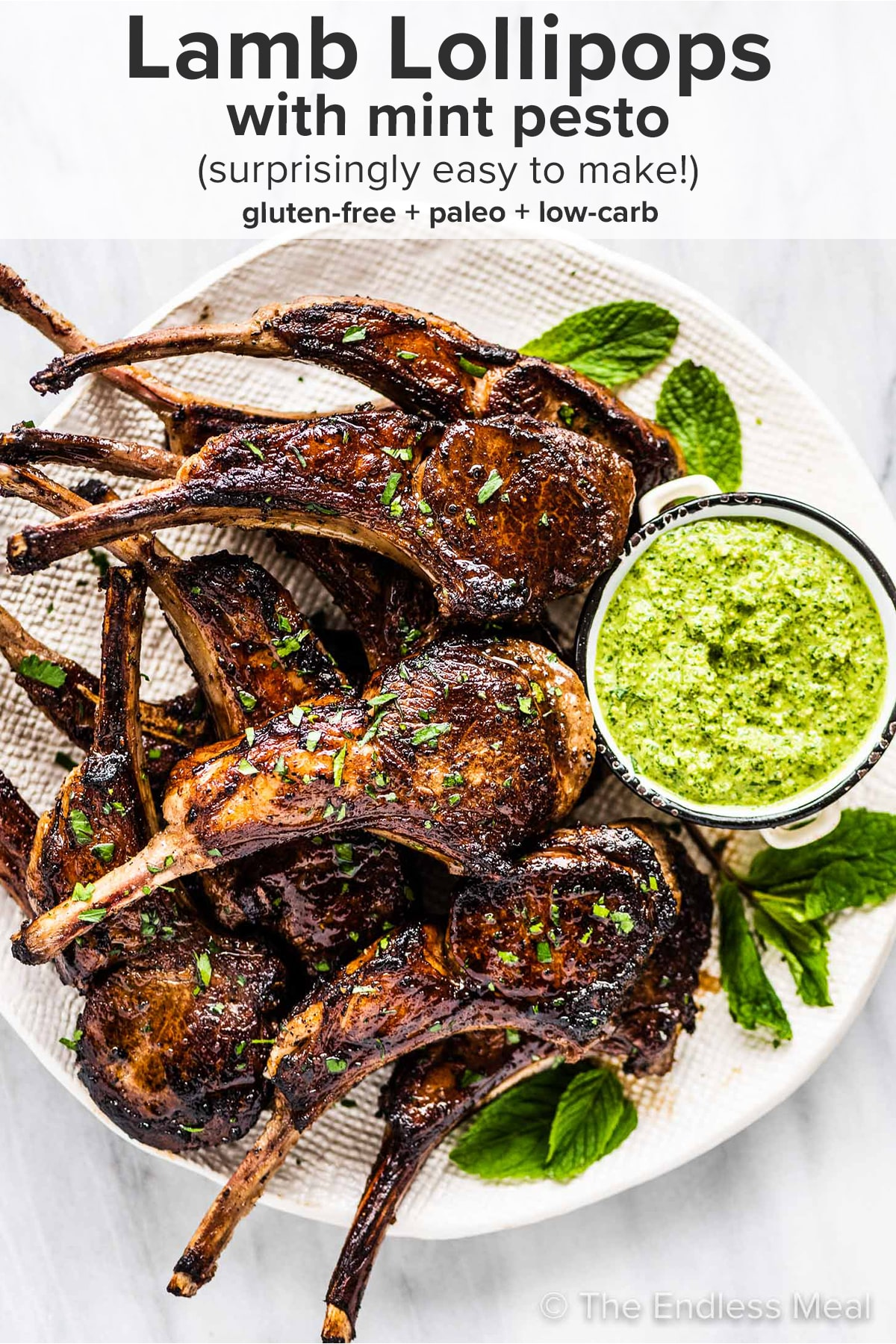 A plate piled with lamb lollipops with mint pesto on the side and the recipe title on top of the picture.