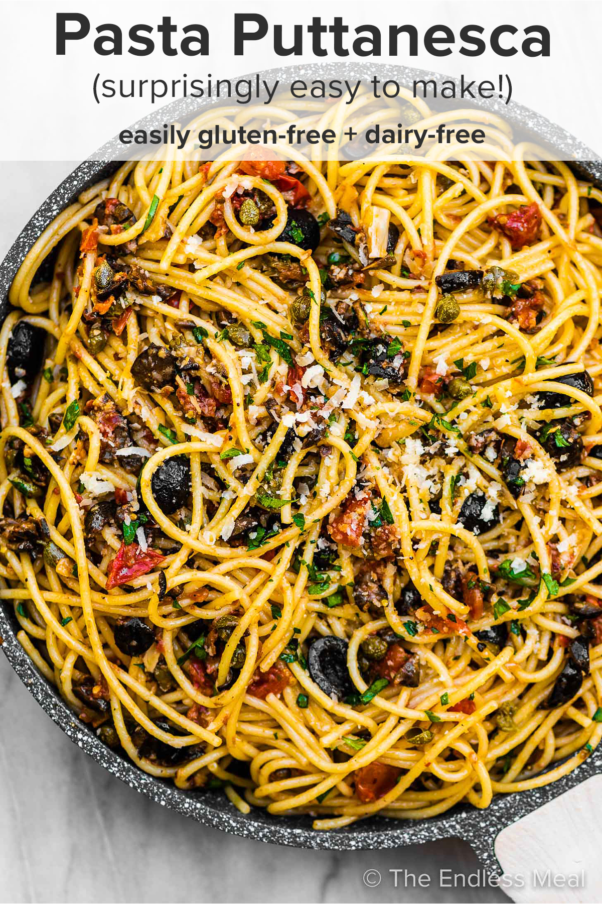 Pasta Puttanesca in a pan with the recipe title on top of the picture.