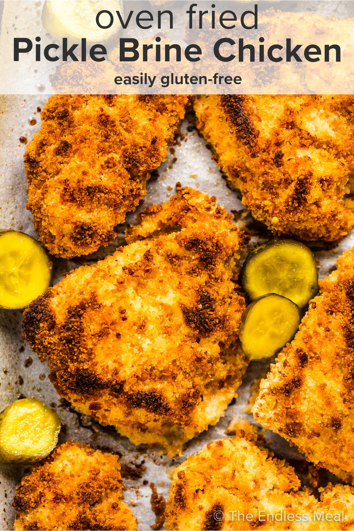 A close up of pickle brine chicken on a baking sheet with pickles and the recipe title on top of the picture.