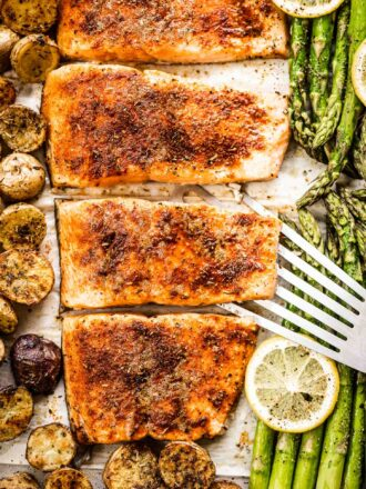 Sheet pan salmon on a baking sheet with potatoes and asparagus.