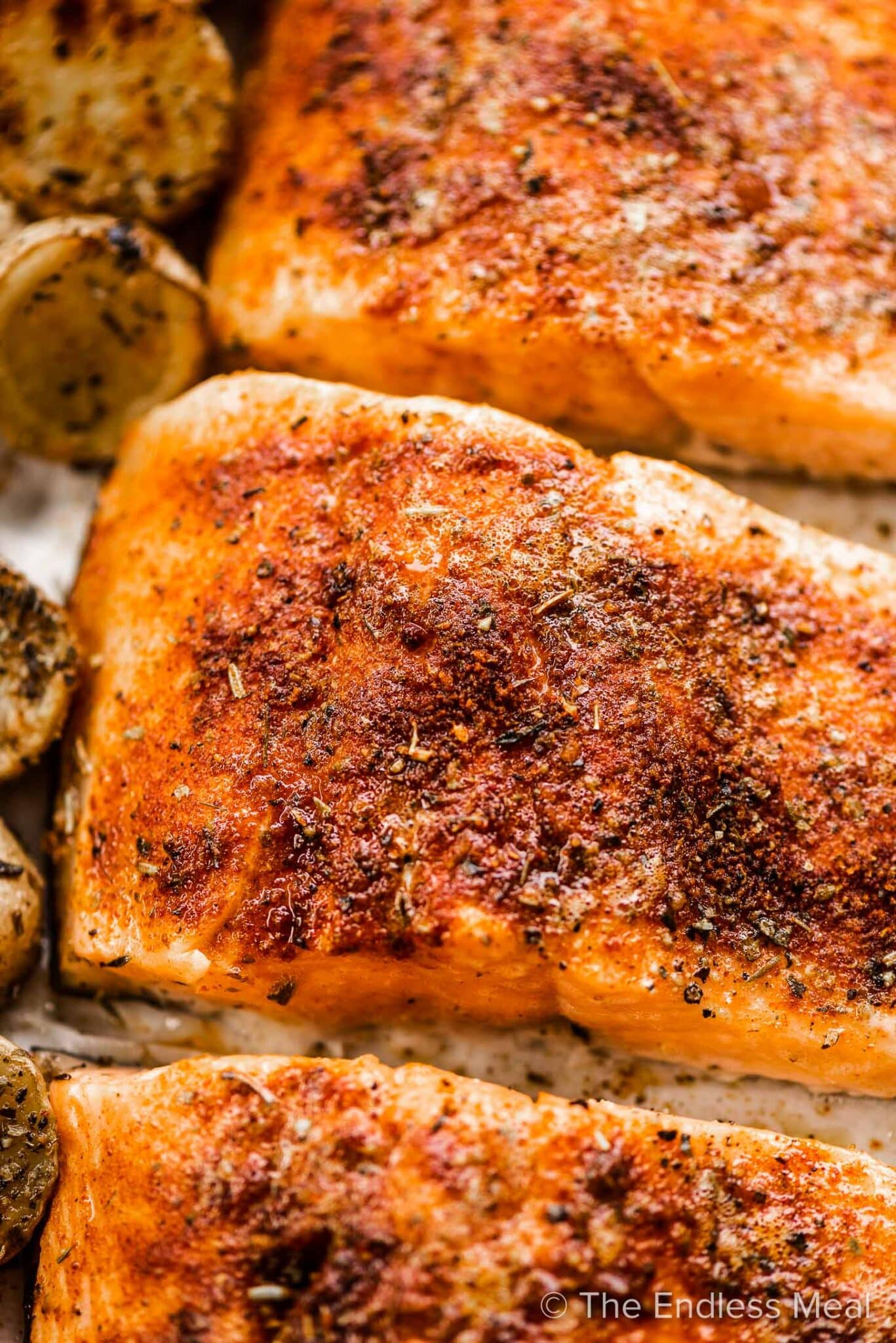 A close up of tender cooked salmon on a baking sheet.