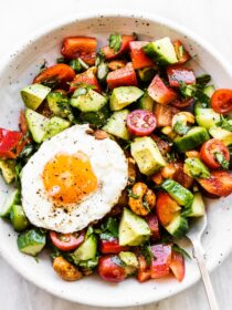 Healthy Breakfast Salad in a white bowl with a fried egg on top.