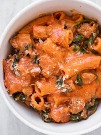 Creamy Italian sausage pasta in a white bowl.
