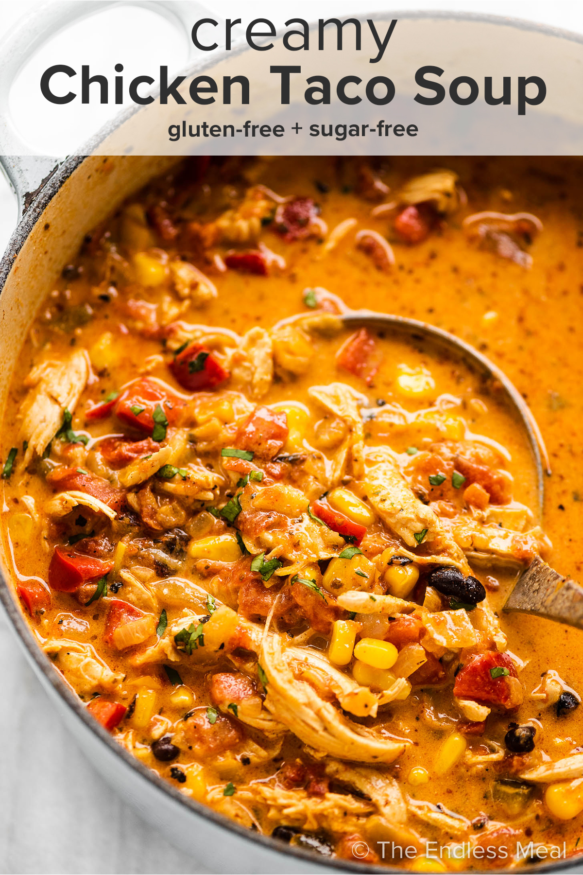 A pot of creamy chicken taco soup with a ladle scooping some out and the recipe title on top of the picture.