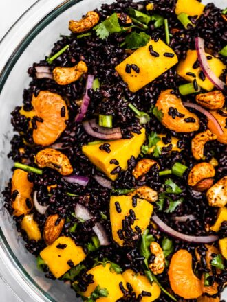 A close up of black rice salad with mango and cashews.