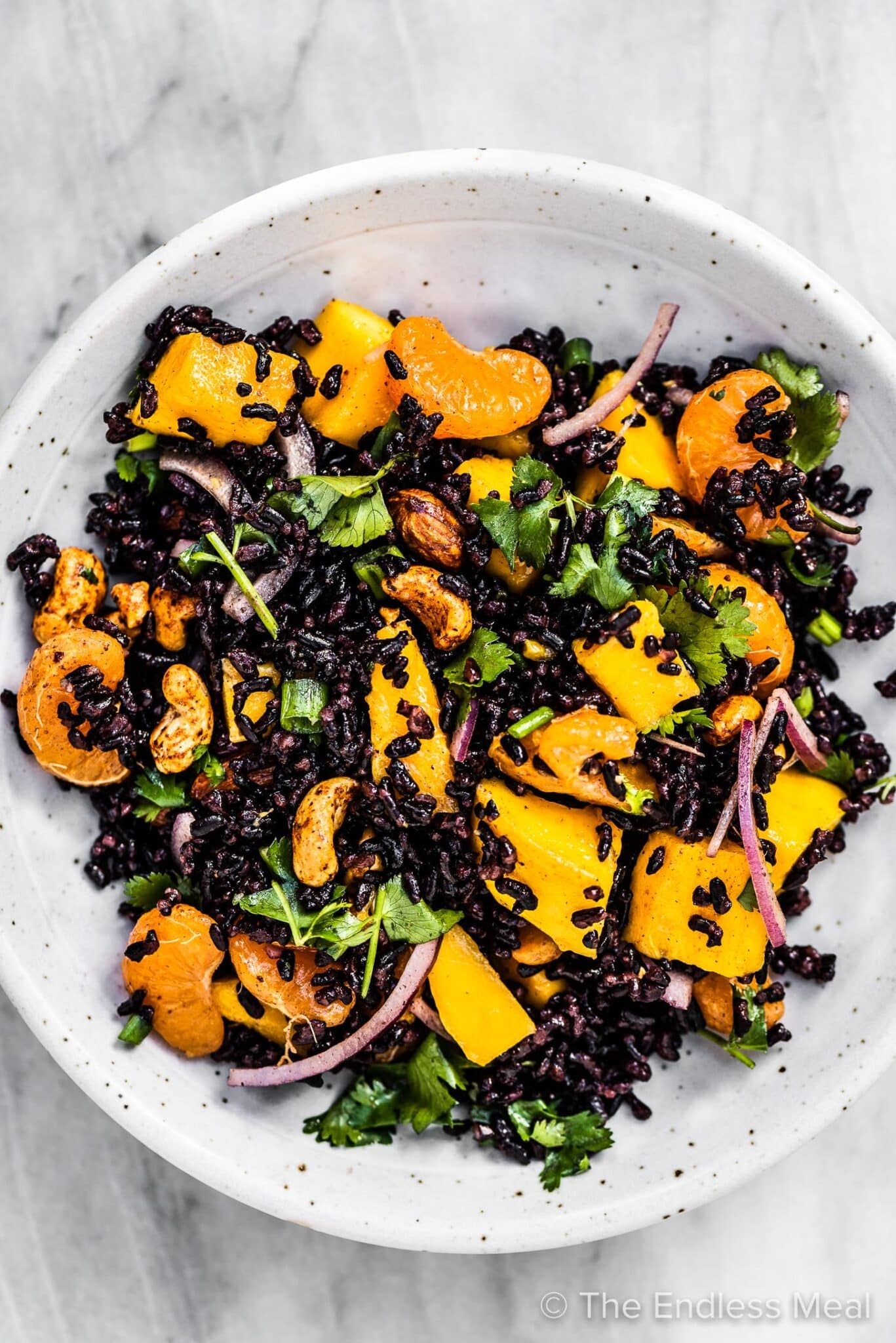 Black rice salad with mangos in a white bowl.