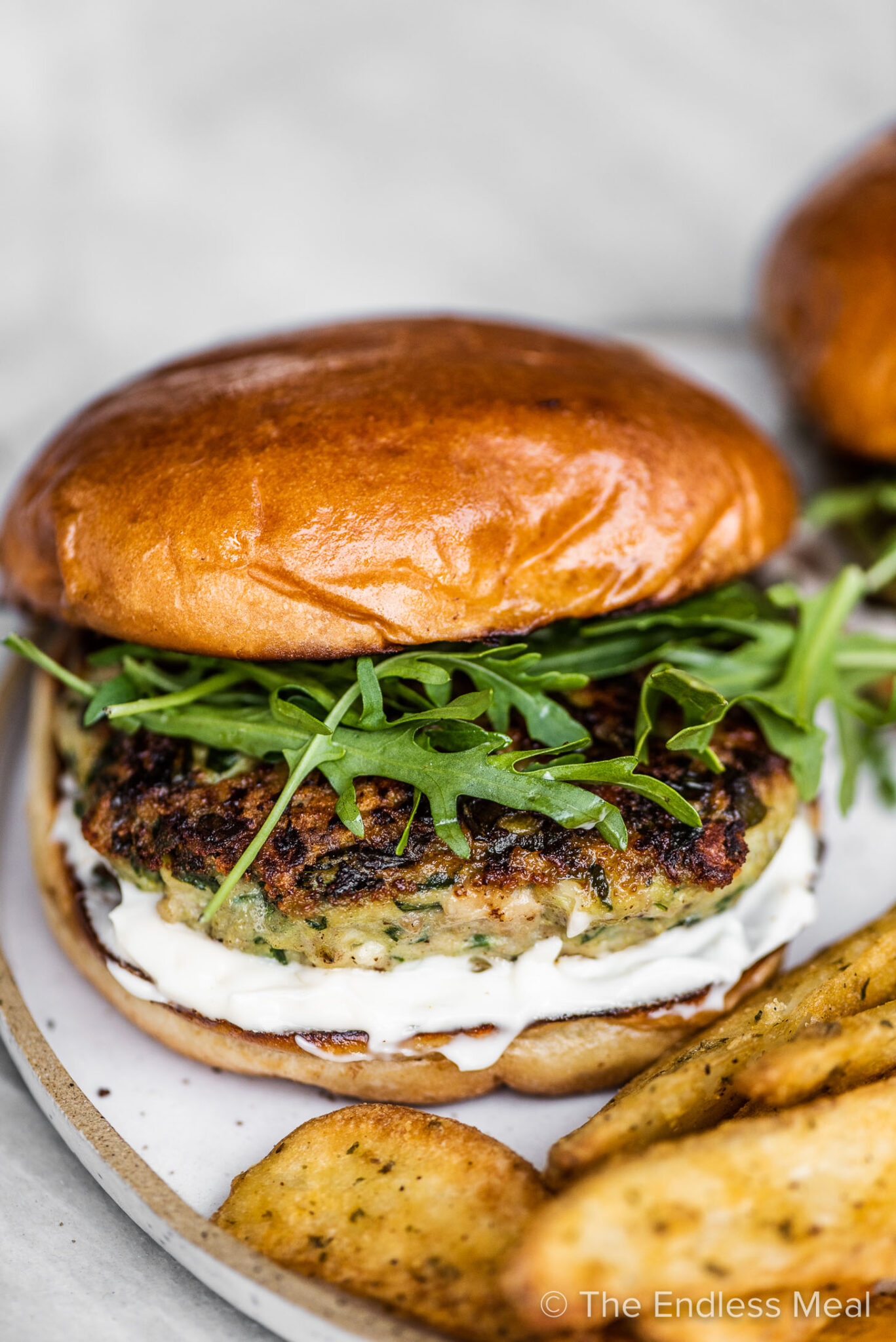 A chicken feta spinach burger on a white plate with fries.