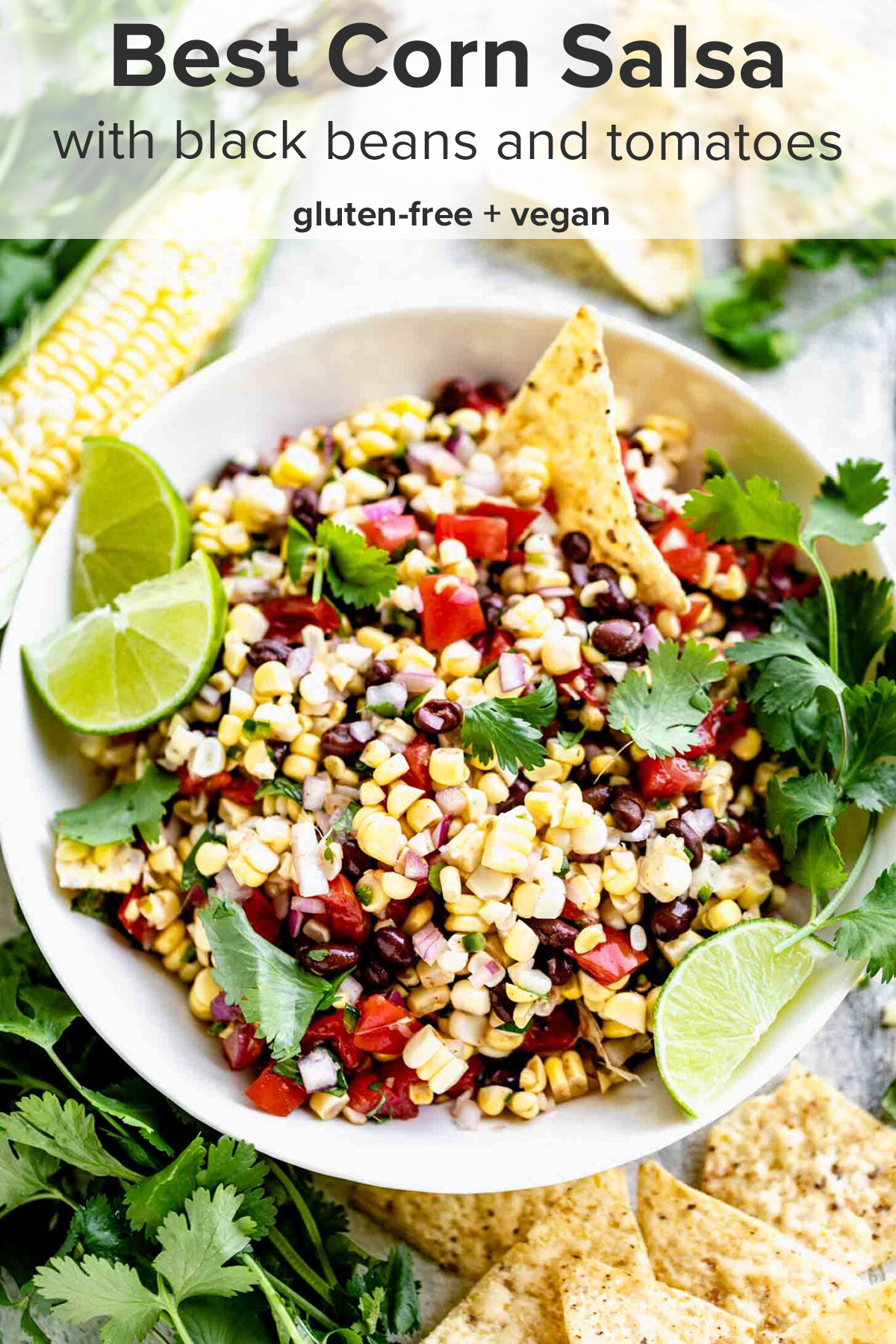 a bowl of corn salsa with a chip in it, garnished with cilantro sprigs and lime wedges and the recipe title on top of the image.