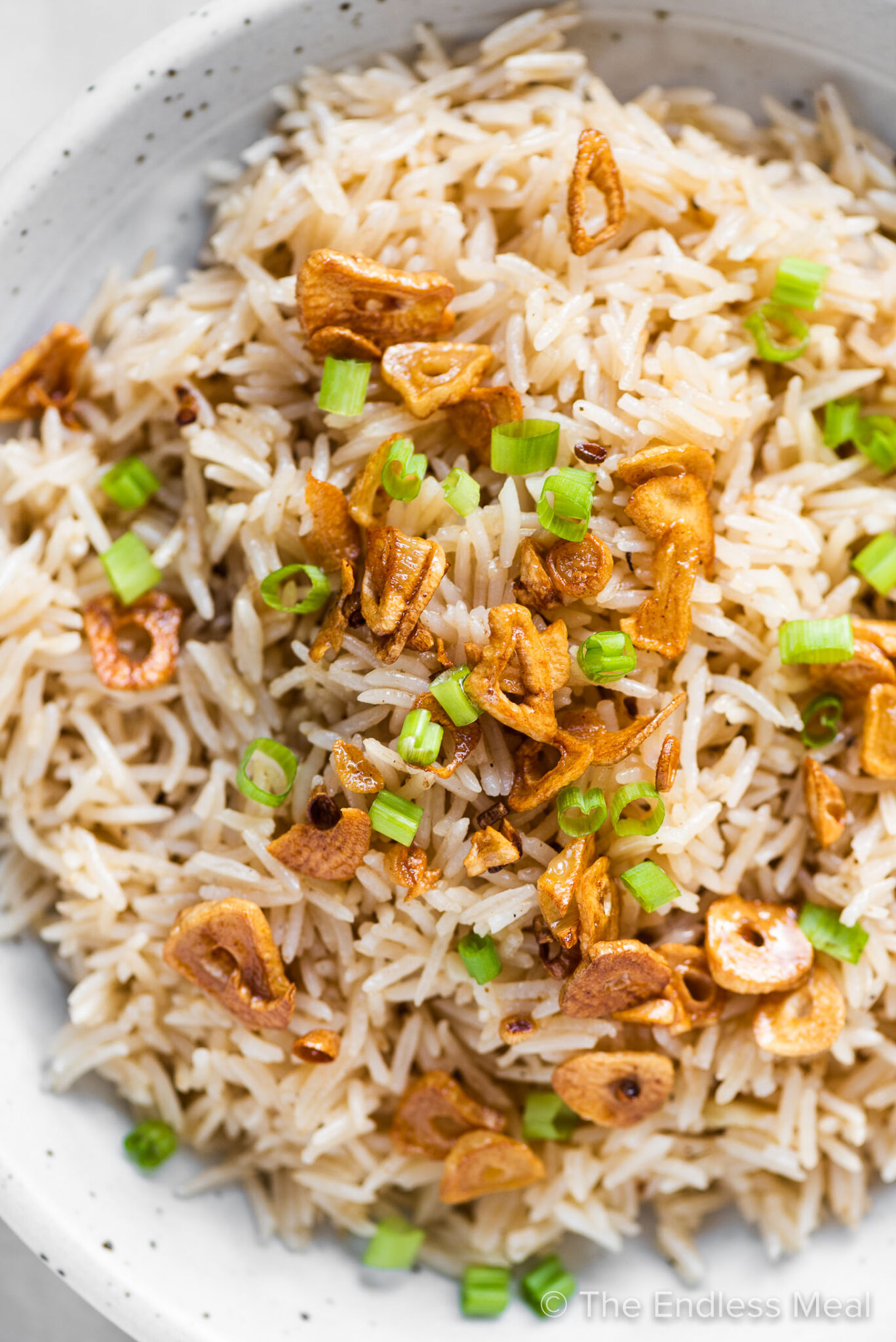 A close up of garlic butter rice with crispy garlic and scallions on the top.