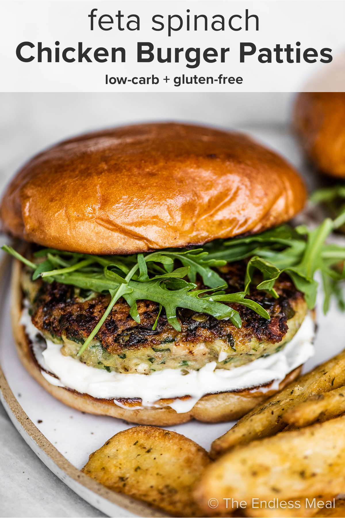 A chicken feta spinach burger on a white plate with fries and the recipe title on top of the picture.