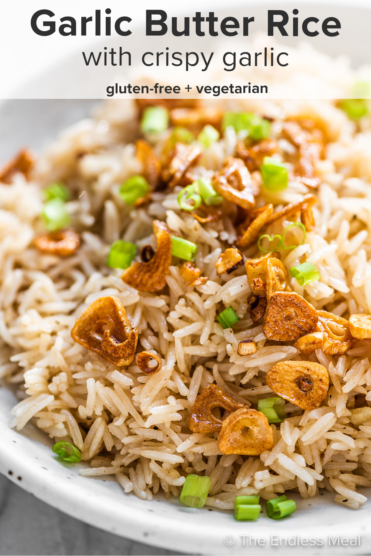 Garlic butter rice in a serving dish topped with crispy garlic and the recipe title on top of the picture.