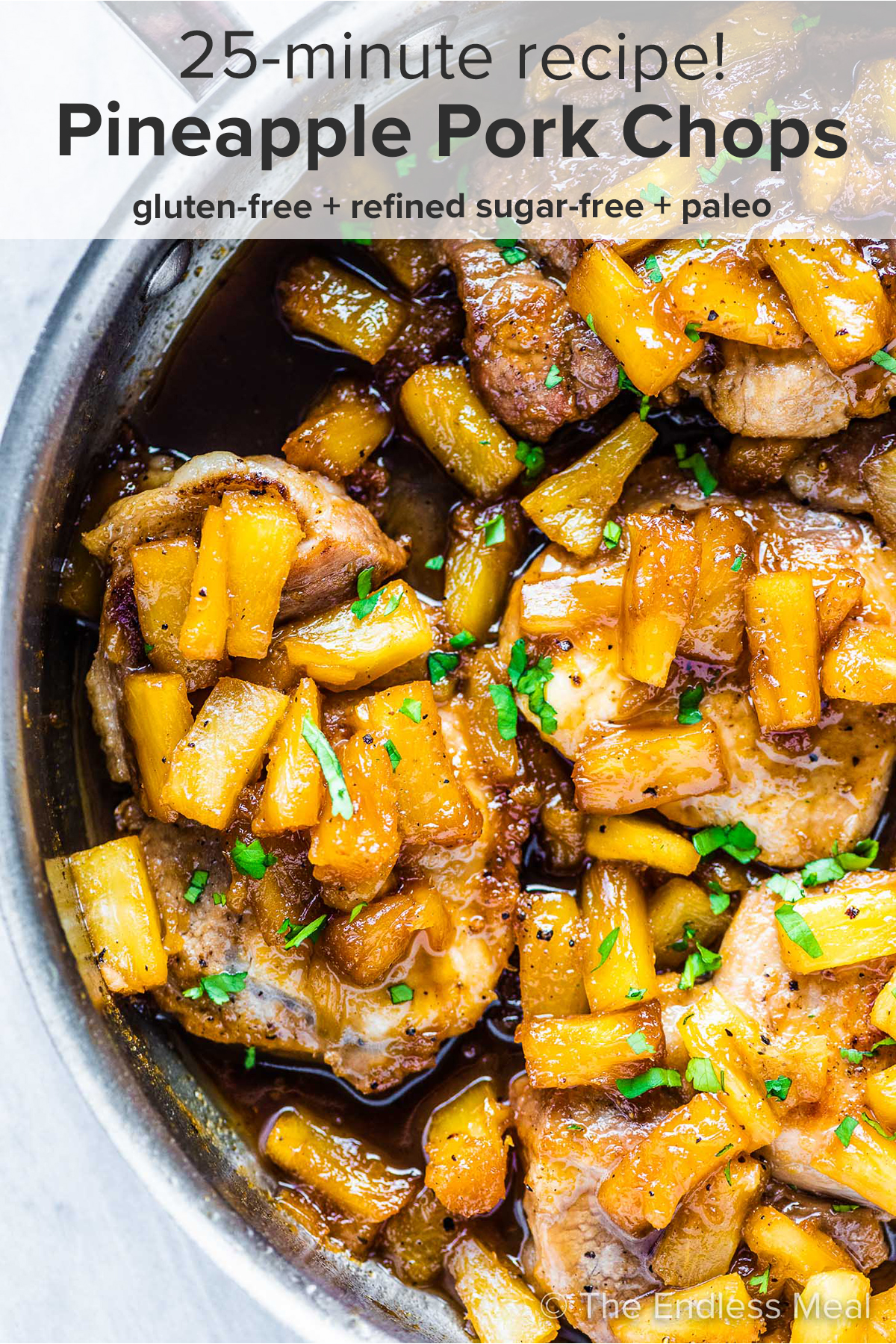 Pineapple pork chops in a pan with the recipe title on top of the picture.